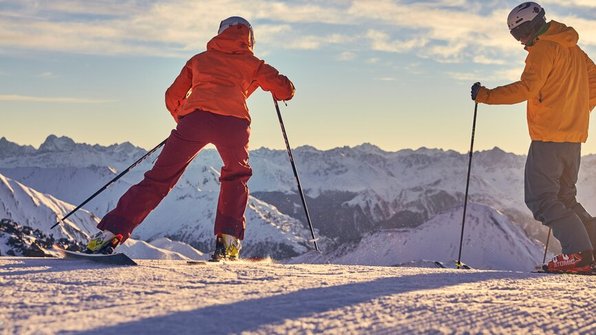 Skiers start into a sunny day with a downhill slope and panoramic mountain view in the ski area of Ischgl