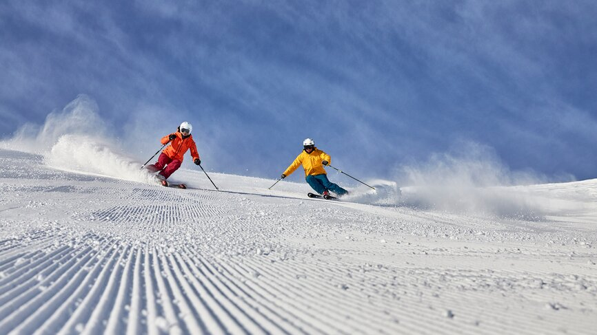 Skiers drive down a slope of the ski area of Ischgl on a sunny day